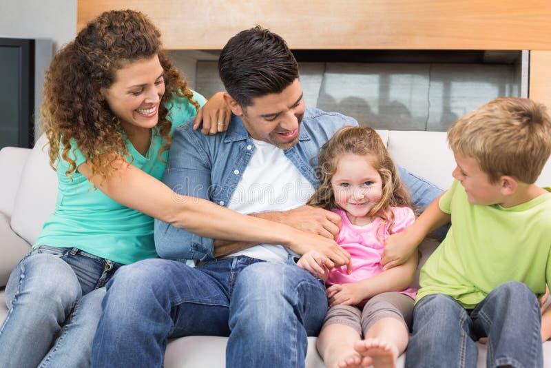 Gullig familj som killar lilla flickan på soffan royaltyfri fotografi