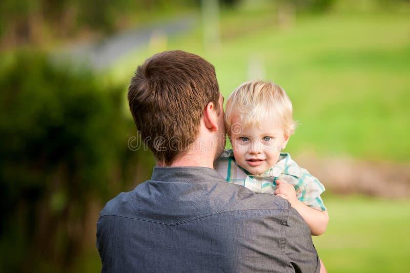 gullig farsa för pojke hans little över skulder för jämliken s arkivbilder