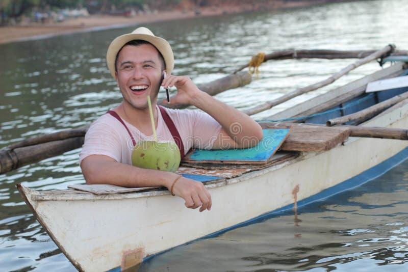 Gullig fiskare som stannar till telefonen arkivbild