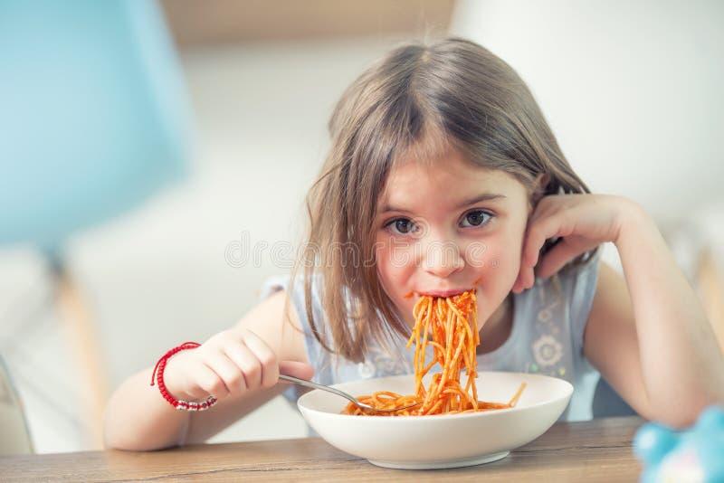 Gullig flicka för liten unge som hemma äter spagetti bolognese royaltyfria bilder