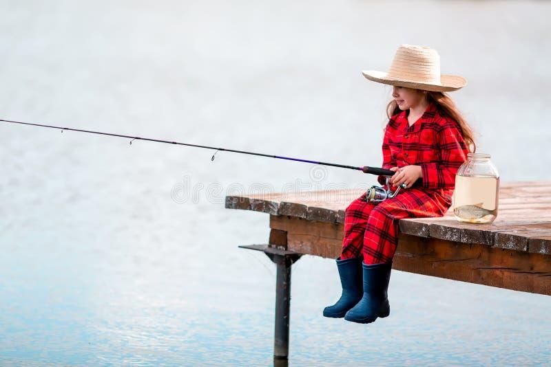 Gullig flicka för litet barn i gummistövel- och för sugrörhatt fiske från träpir nära exponeringsglaskruset och liten fisk på en  arkivbild