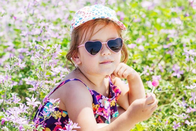 Gullig flicka för litet barn med en klubba utomhus arkivfoton