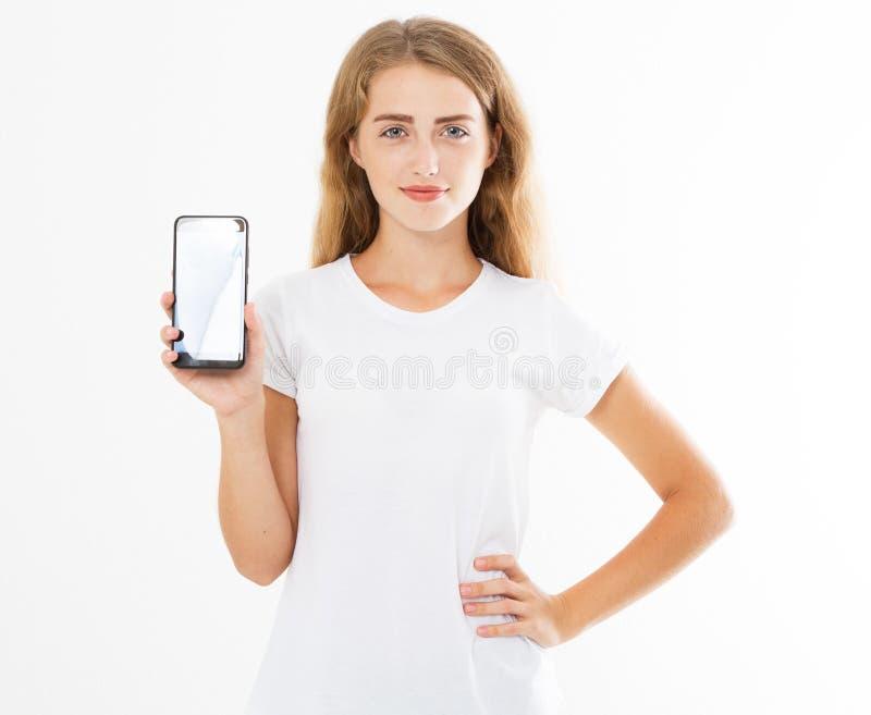 Gullig flicka f?r leende, kvinna i mobiltelefonen f?r tom sk?rm f?r tshirth?ll som isoleras p? vit bakgrund Smartphone f?r arminn arkivfoto