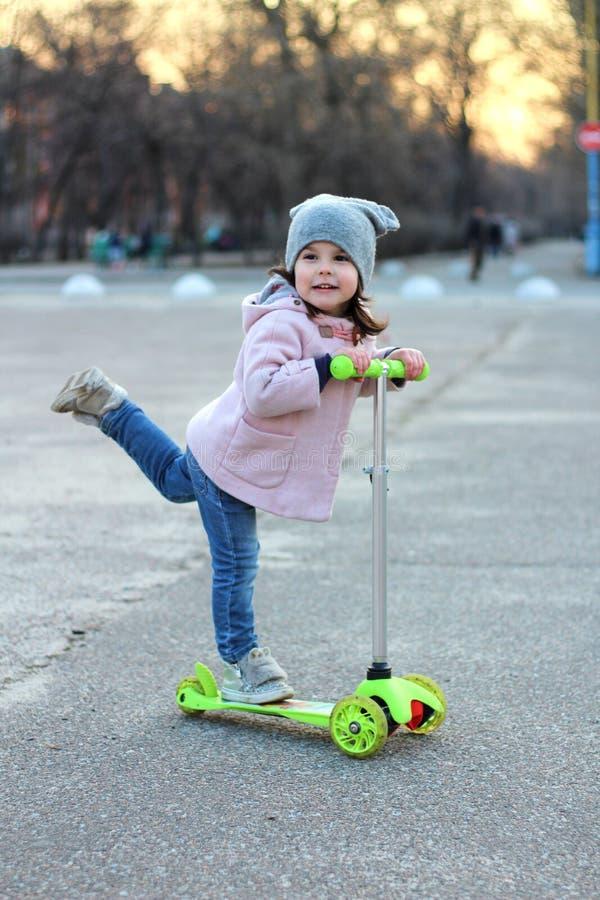 Gullig flicka i en hatt, ett lag och en jeans som rider enrullad sparkcykel Solnedgång för aftonvårstad arkivbilder