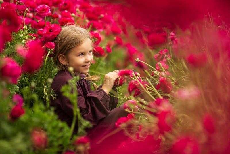 Gullig flicka i fält av vildblommor i den öppna luften Flickan i smörblomman Lycklig unge med smörblomman arkivfoto
