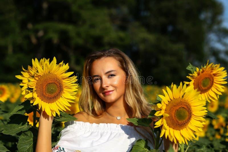 Gullig flicka i f?ltet mycket av solrosor arkivbilder