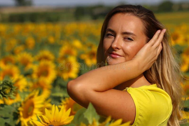 Gullig flicka i f?ltet mycket av solrosor royaltyfria bilder