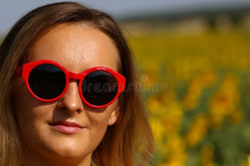 Gullig flicka i f?ltet mycket av solrosor arkivfoto
