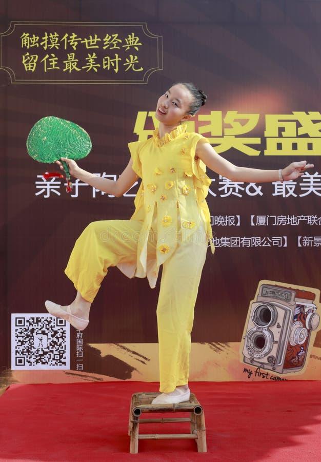 Gullig flicka i gul kapacitetsfandans på liten bambustol royaltyfri foto