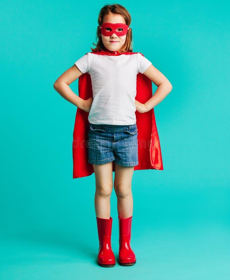 Gullig flicka i röd superherodräkt arkivfoton