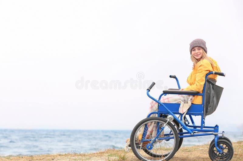 Gullig flicka i rullstol på havet arkivbilder