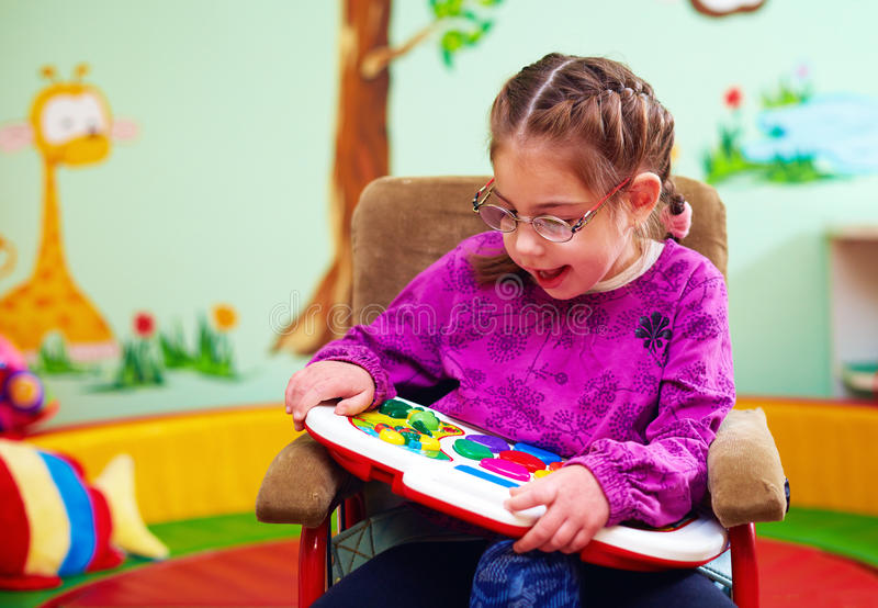 Gullig flicka i rullstolen som spelar med den framkallande leksaken i dagiset för barn med speciala behov arkivfoto