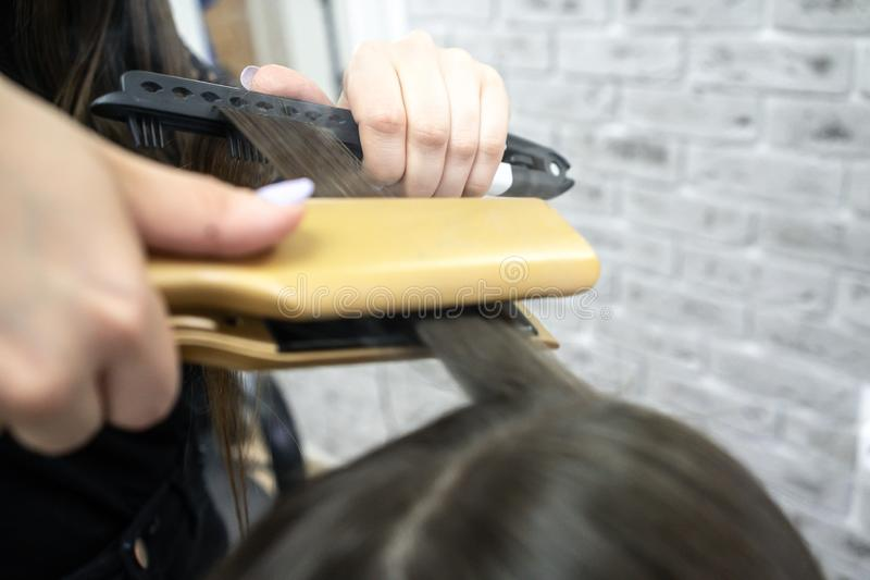 Gullig flicka med den långa brunetthårfrisören som gör hårlamination i en skönhetsalong begrepp av behandling för håromsorg arkivfoto