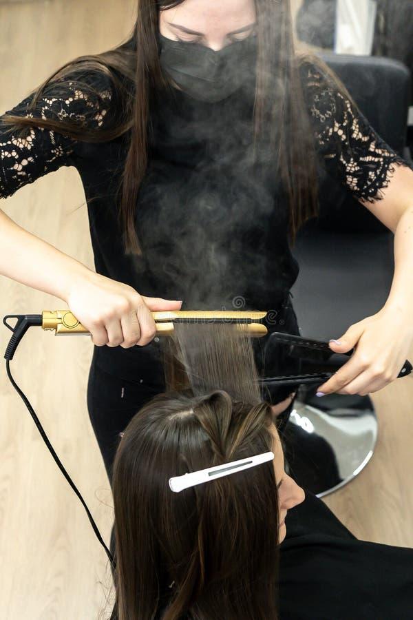 Gullig flicka med den långa brunetthårfrisören som gör hårlamination i en skönhetsalong begrepp av behandling för håromsorg arkivbild