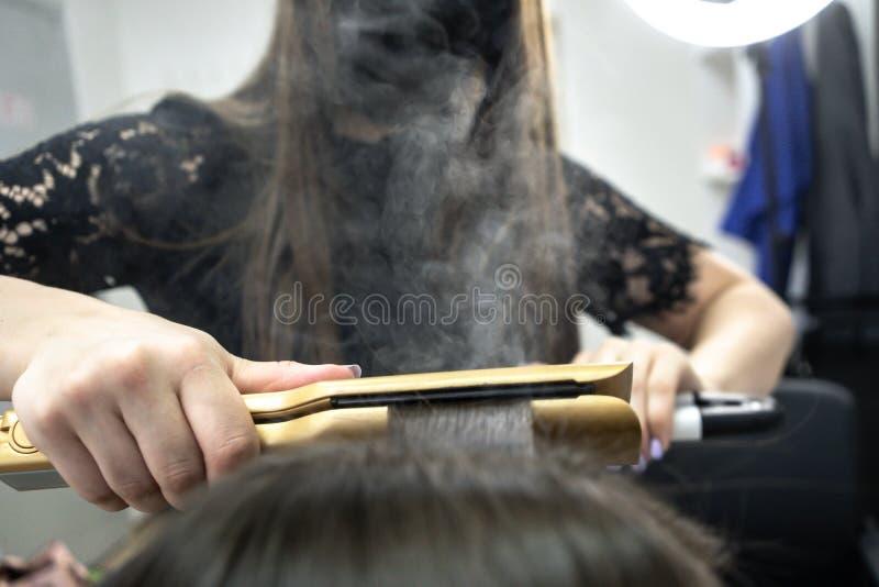Gullig flicka med den långa brunetthårfrisören som gör hårlamination i en skönhetsalong begrepp av behandling för håromsorg royaltyfri fotografi