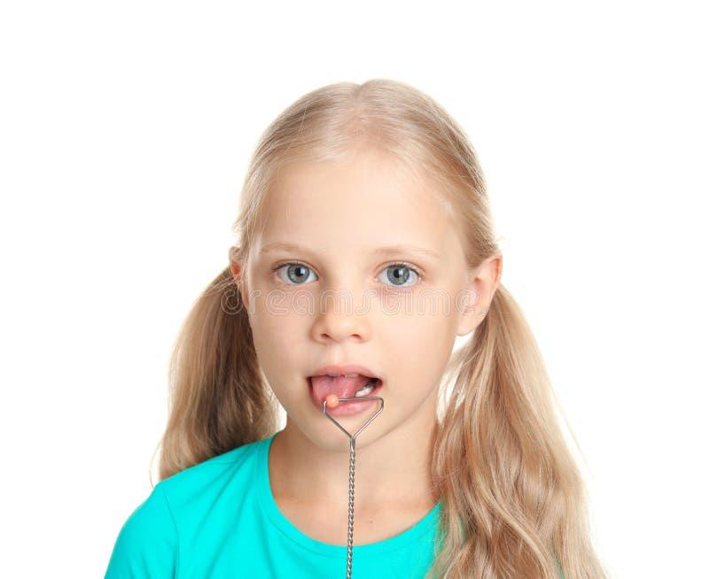 Gullig flicka med den logopedic sonden för anförandekorrigeringen på vit bakgrund arkivfoton