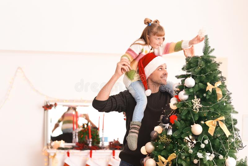 Gullig flicka med fadern som dekorerar julgranen i rum arkivbilder