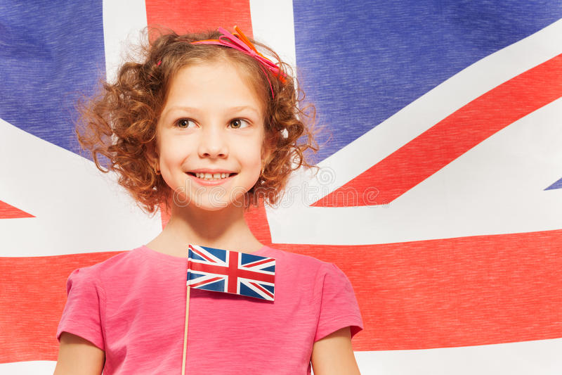 Gullig flicka med flaggan, baner av England bakom royaltyfri bild