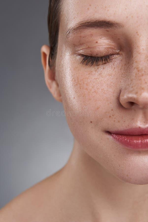 Gullig flicka med fräknar som står mot grå bakgrund arkivfoto
