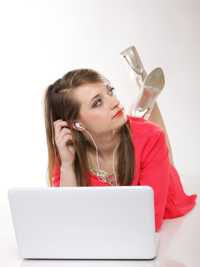 Gullig flicka med hörlurar och att ligga för bärbar dator royaltyfri foto