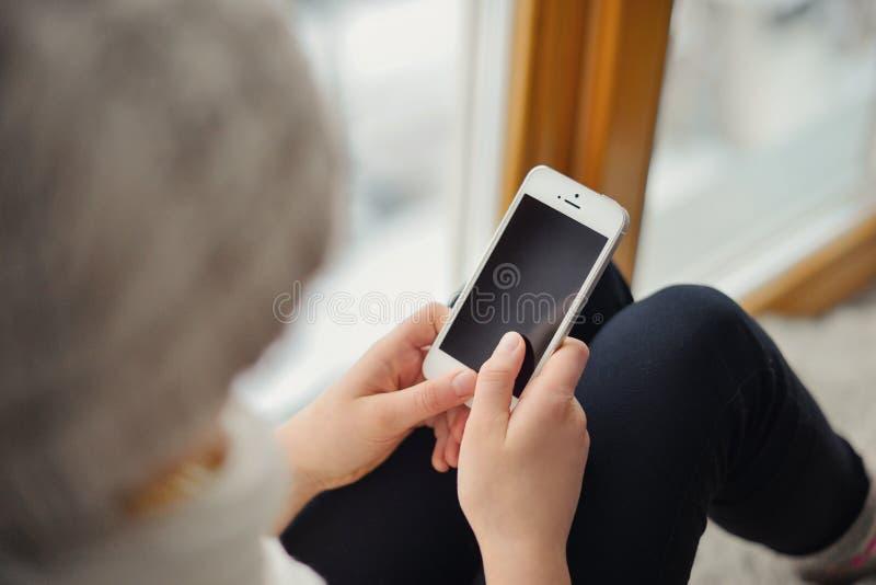 Gullig flicka med långt hår som sitter det ensamma near fönstret med mobiltelefonen royaltyfria bilder