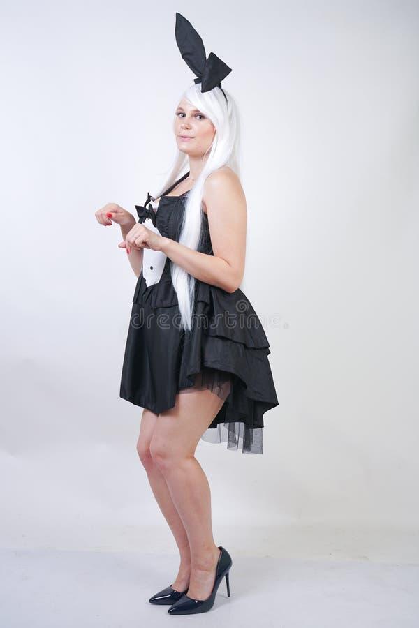 Gullig flicka med långt vitt hår med kaninöron i kanindräkt på vit bakgrund i studio en kvinna med a plus den stan formatkroppen arkivbilder