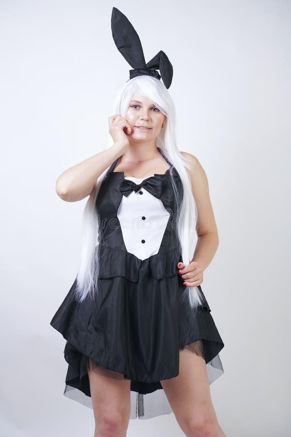 Gullig flicka med långt vitt hår med kaninöron i kanindräkt på vit bakgrund i studio en kvinna med a plus den stan formatkroppen arkivfoto
