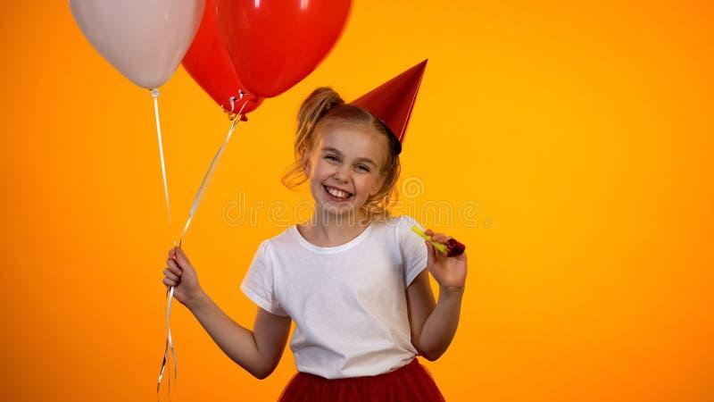 Gullig flicka med luftballonger och partiblåsare som ler till kameran, beröm royaltyfri bild