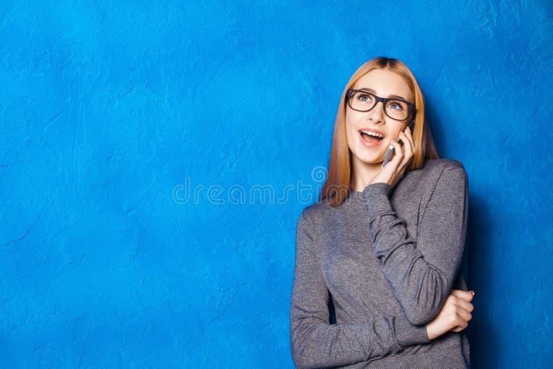 Gullig flicka mot den blåa väggen royaltyfria bilder