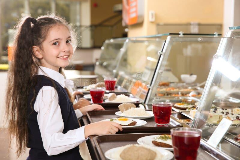 Gullig flicka nära tjänande som linje med sund mat i kantin arkivfoto