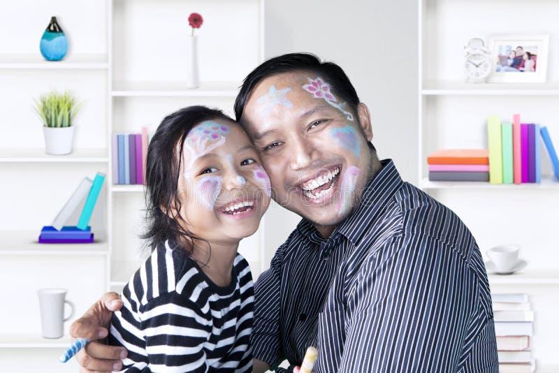 Gullig flicka och fader som har gyckel hemma arkivfoto