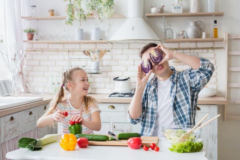 Gullig flicka och hennes farsa som har gyckel, medan laga mat i kök royaltyfri foto