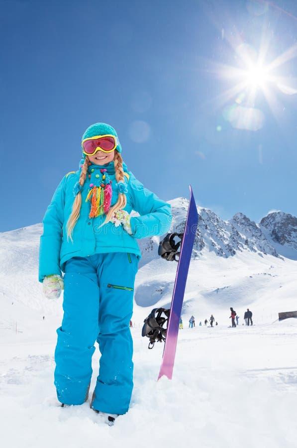 Gullig flicka och hennes snowboard royaltyfri foto