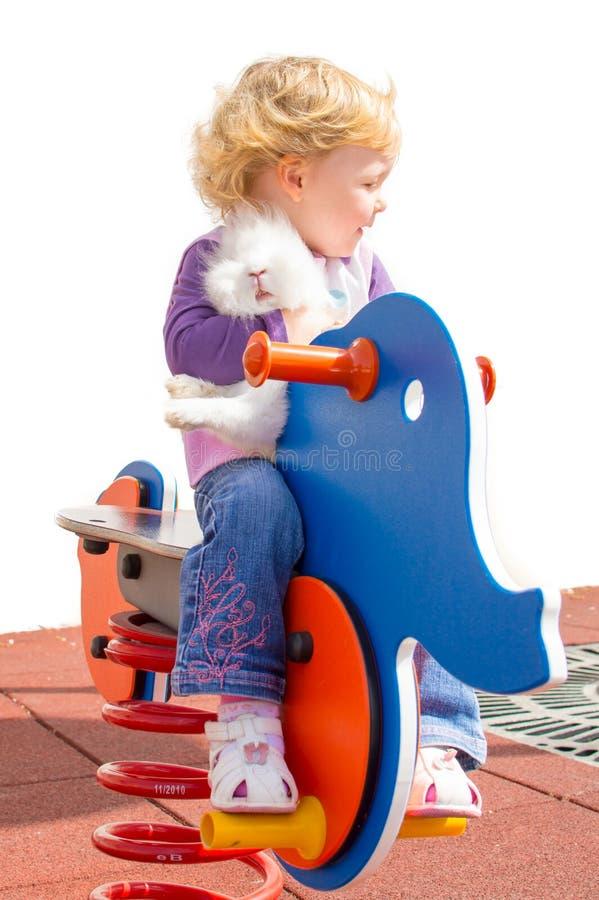Gullig flicka och kanin på lekplatsen arkivfoto