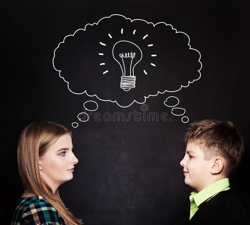 Gullig flicka och pojke med lightbulben på svart tavla arkivbild