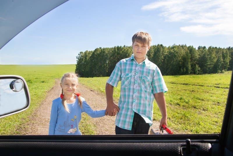 Gullig flicka och pojke med resväskan royaltyfri fotografi