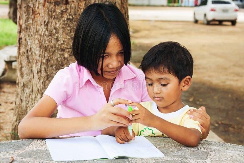 Gullig flicka- och pojkehandstil på boken fotografering för bildbyråer