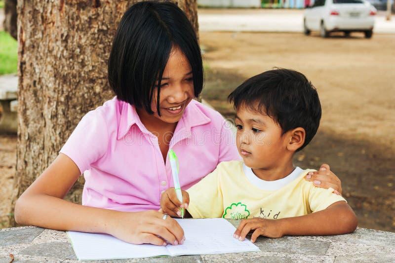 Gullig flicka- och pojkehandstil på boken royaltyfria foton