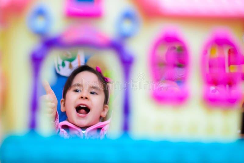Gullig flicka på bakgrunden av hennes le för leksaker arkivfoton