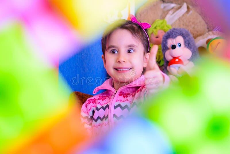 Gullig flicka på bakgrunden av hennes le för leksaker royaltyfri bild