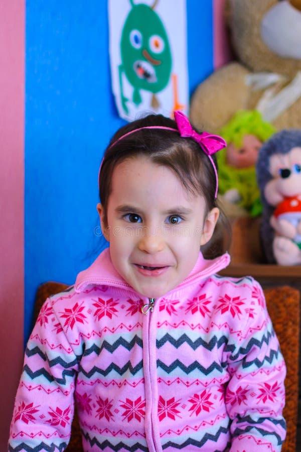 Gullig flicka på bakgrunden av hennes le för leksaker royaltyfri foto