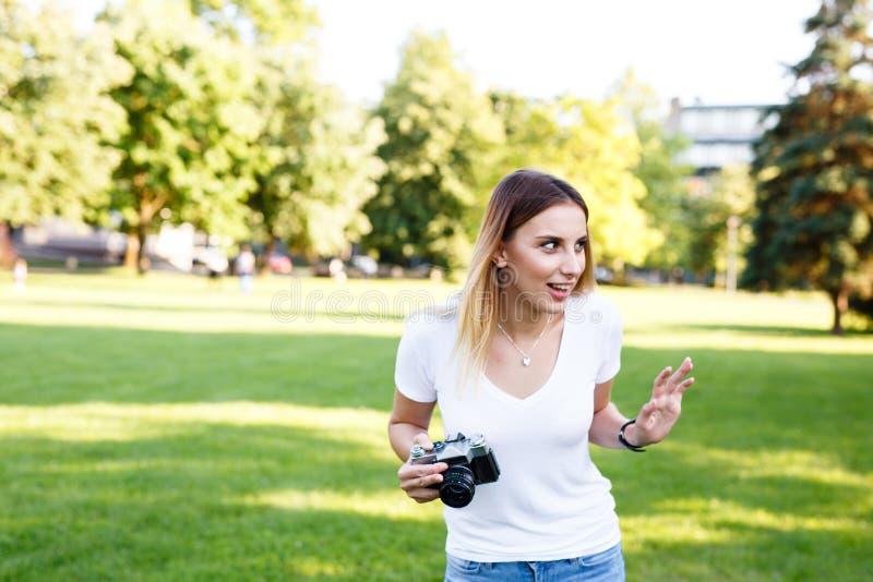 Gullig flicka på solig dag i parkering som går med hennes kamera arkivfoton