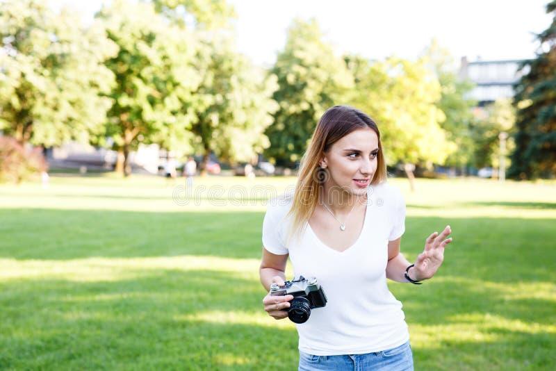 Gullig flicka på solig dag i parkering som går med hennes kamera royaltyfria foton