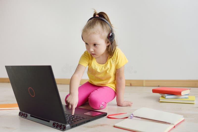 Gullig flicka som är online- på bärbara datorn Barnet sitter på internet fotografering för bildbyråer