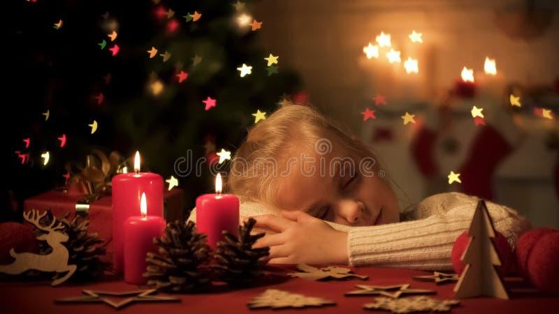 Gullig flicka som är stupad sovande på tabellen som dekoreras för julberöm, hemtrevligt hem arkivbilder