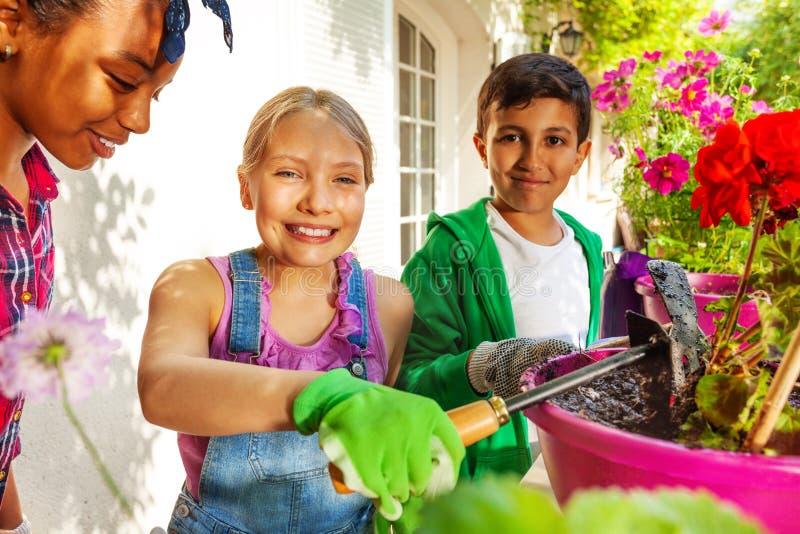 Gullig flicka som arbetar i trädgård med hennes vänner royaltyfri bild