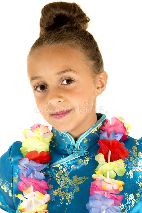 Gullig flicka som bär en kinesisk klänning och le för lei royaltyfria foton