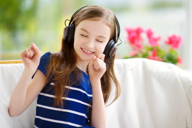 Gullig flicka som bär enorm trådlös hörlurar Nätt barn som lyssnar till musiken Skolflicka som har gyckel som lyssnar till sånger royaltyfri bild