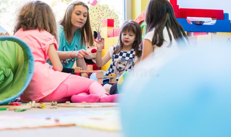 Gullig flicka som bygger en struktur från leksakkvarter under rast royaltyfria bilder