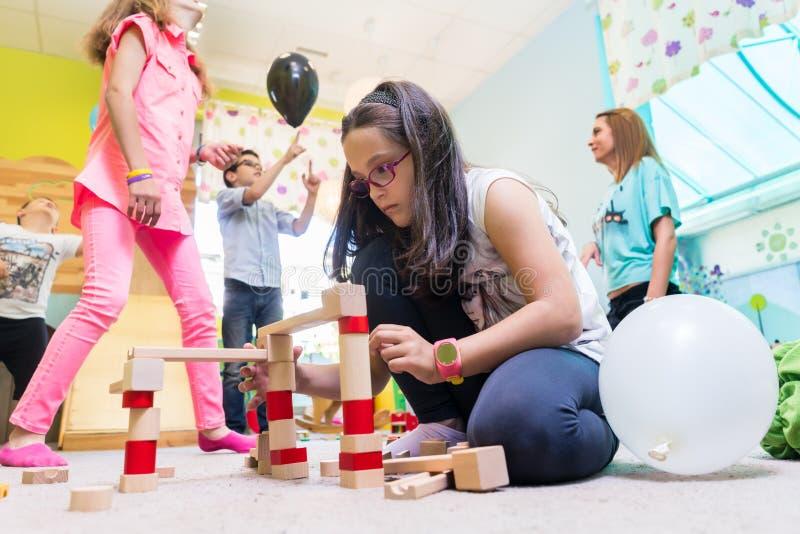 Gullig flicka som bygger en struktur i jämvikt under rast på dagiset royaltyfri fotografi
